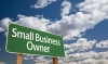 Small Business Owner Green Road Sign with Dramatic Clouds and Sky.